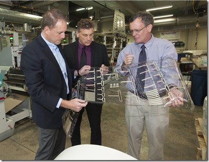 Charles 'Chip' Tonkin (left), Steve Foulger and Liam O'Hara, examine flexible hybrid electronics produced on a Clemson press. (Photo provided by Clemson University)