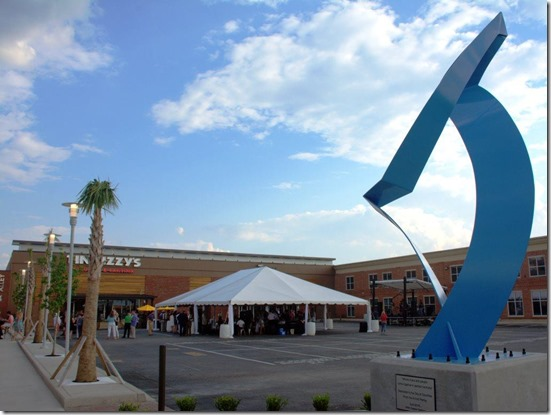 Miami-based artist Stephen Gamson created the abstract sculpture (above), representing  the treble clef musical signature, to celebrate the harmony of people and rivers coming together in Columbia. Patrons enjoy the new outdoor dining area (below) at the Arnold Companies' West End Alley  entertainment complex. (Photos/Chuck Crumbo)