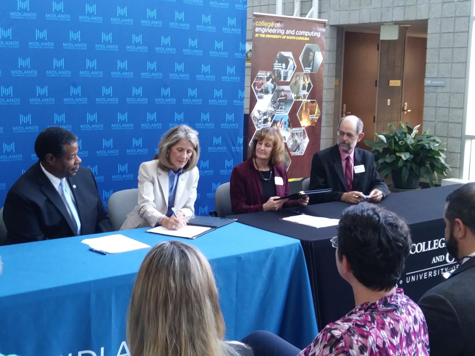 Midlands Technical College President Ronald Rhames (from left) and provost Barrie Kirk; Sandra Kelly, vice provost and dean of undergraduate students at the University of South Carolina; and Jed Lyons, associate dean of academic affairs at USC, sign a transfer agreement. (Photo/Travis Boland)