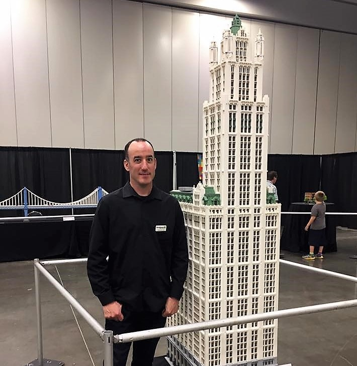 Lego artist Jonathan Lopes with his 8-foot replica of the Woolworth Tower in New York City. (Photo/Provided)