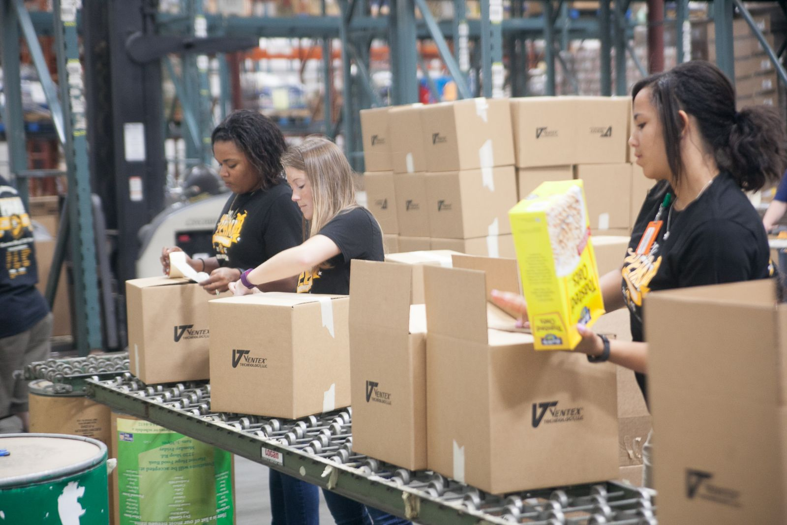 Amazon employees help box food at Harvest Hope Food Bank.