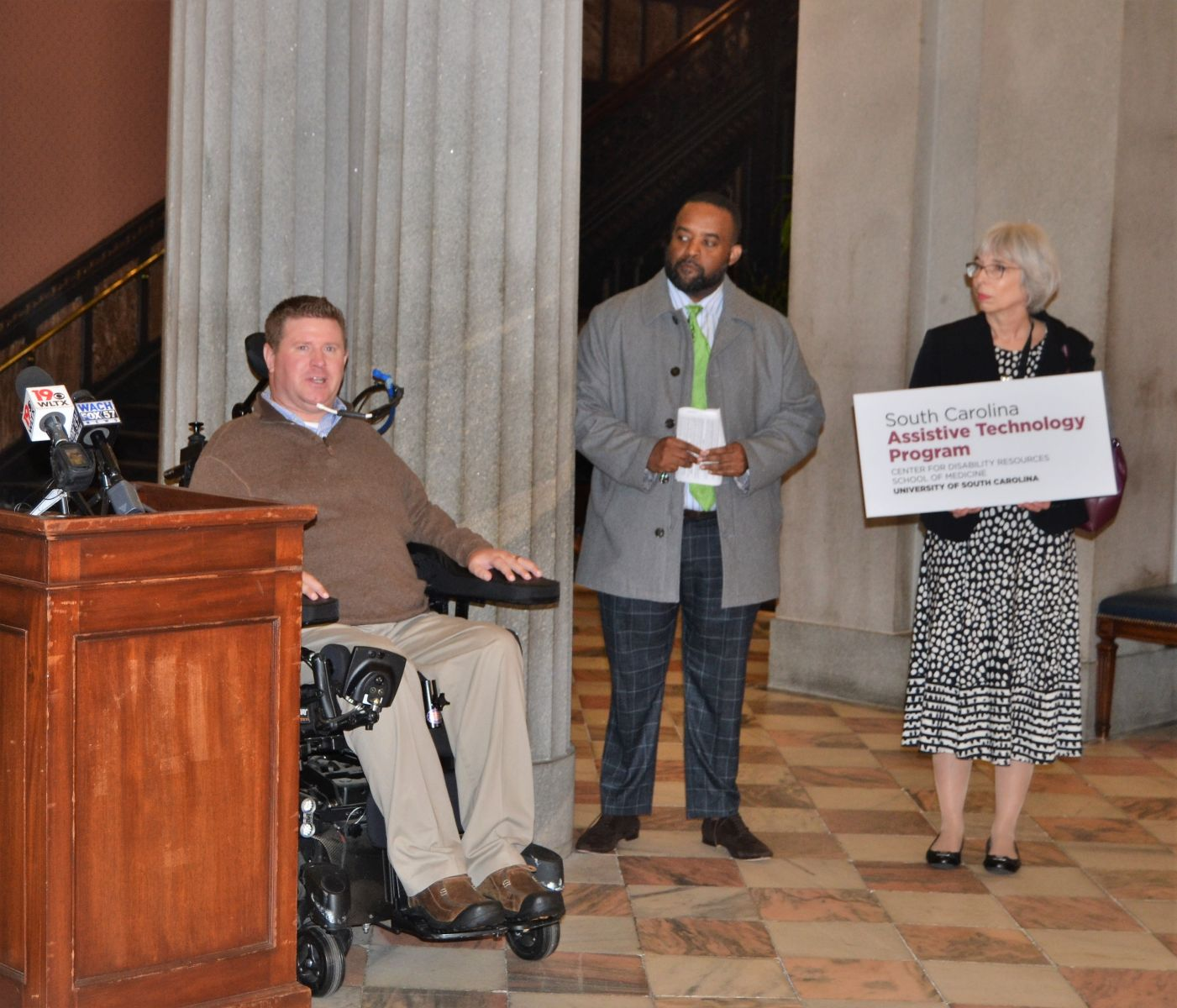 Brian Denny (left), outreach coordinator at the S.C. Spinal Cord Injury Association, speaks during a Feb. 26 ceremony at the Statehouse designating March as Assistive Technology Awareness Month. (Photo/Melinda Waldrop)