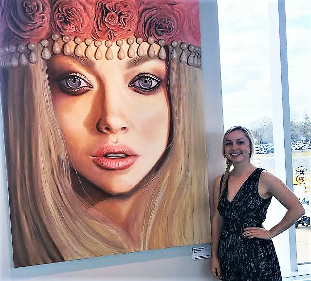 "Local artist Jennifer Hoskins poses next to her latest work ""Crowned"" being shown at the Columbia Metropolitan Airport. (Photo/Provided)"
