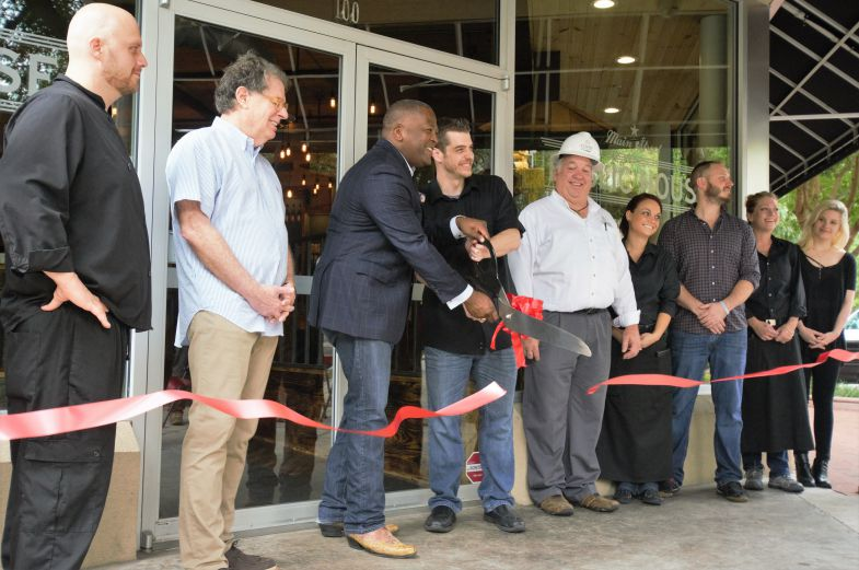 Columbia Mayor Steve Benjamin (center) cuts the ribbon at the Main Street Public House's grand opening on Thursday. (Photo/Chuck Crumbo)