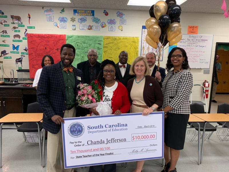 Fairfield Central biology teacher Chanda Jefferson (with roses) learns from S.C. Superintendent of Education Molly Spearman (to her right) that she is one of five finalists for the 2019 S.C. Teacher of the Year award. (Photo/Provided)